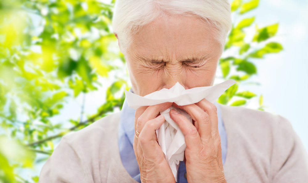 Elderly man blowing nose into a tissue while outdoors