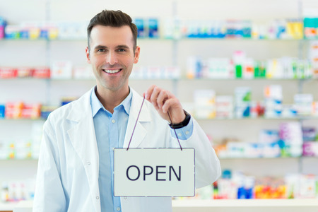 Doctor holding an open sign with blurred shelves in the background